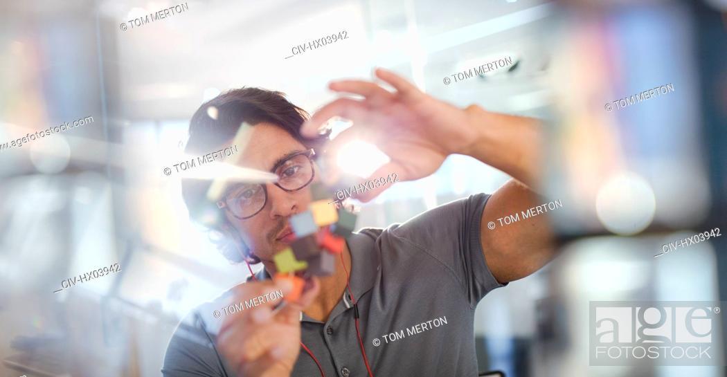 Stock Photo: Focused, innovative male entrepreneur examining prototype.