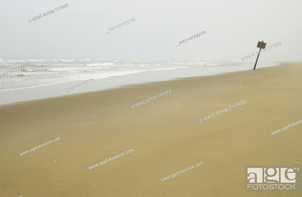 Stock Photo: Sign on flat sandy beach with mist in the background, Reedsport, Oregon.