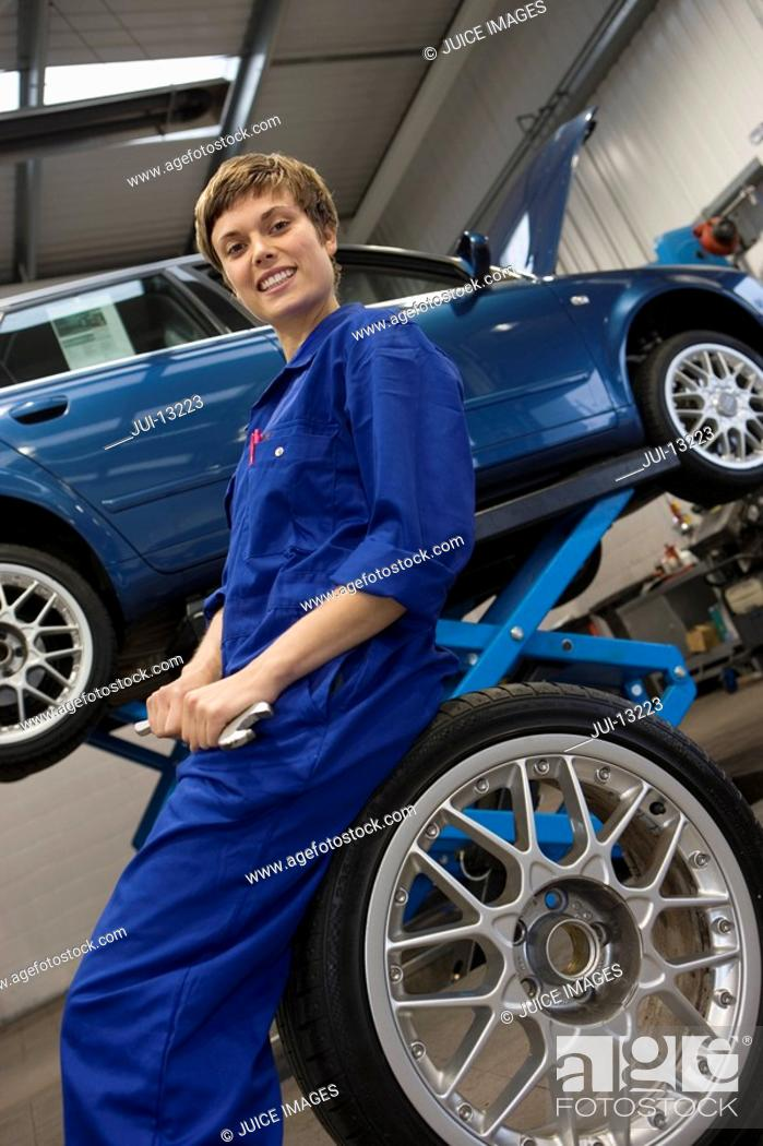 Stock Photo: Female mechanic with wrench on tyre by elevated car, portrait, low angle view.