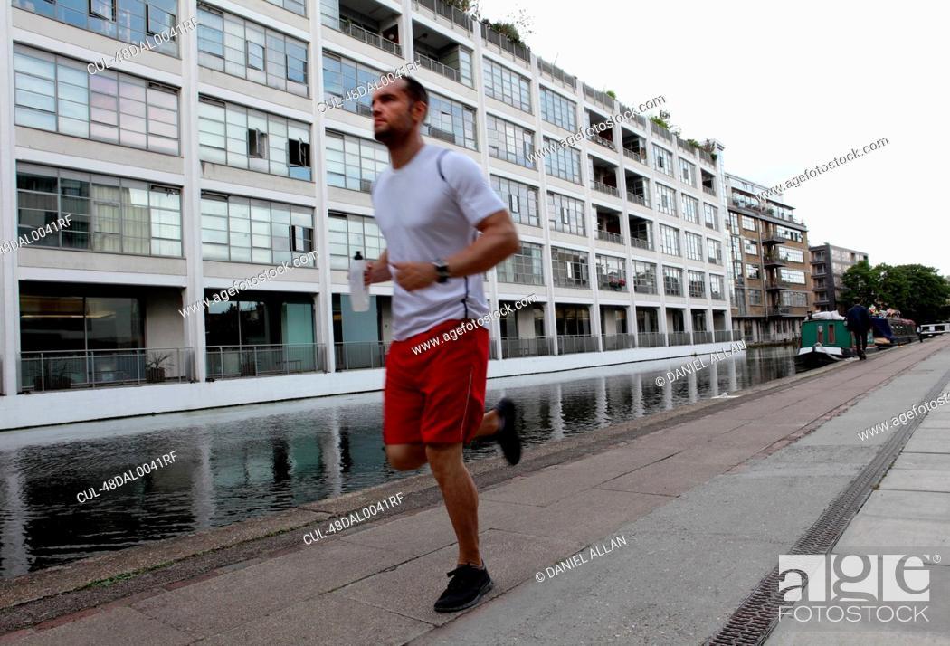 Stock Photo: Man running on city street.