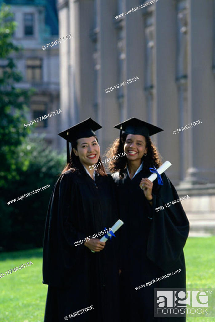 Stock Photo: Portrait of two young women wearing graduation outfits holding diplomas.
