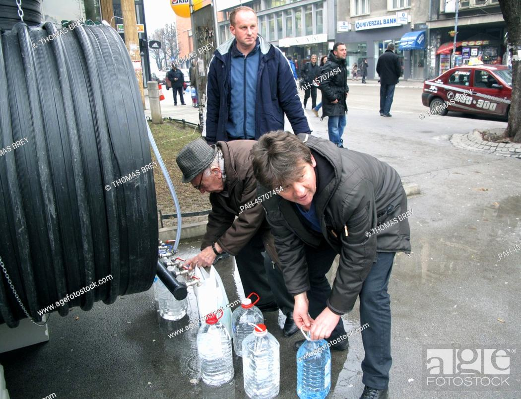 Stock Photo: Residents fill bottles with drinking water from a water barrel in Uzice, Serbia, 17 January 2014. About 6,000 people are living without tab water for four weeks.