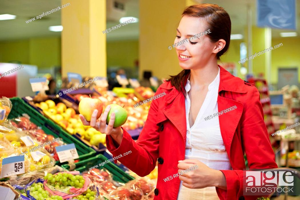 Stock Photo: Germany, Cologne, Young woman comparing apples in supermarket.