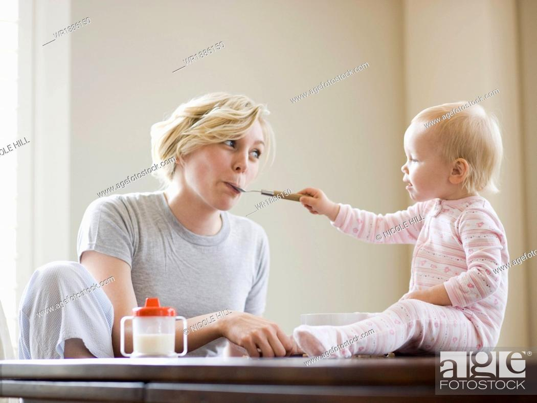 Stock Photo: mother and baby girl at the breakfast table.