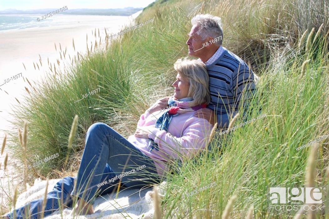 Stock Photo: Senior couple sitting on beach.