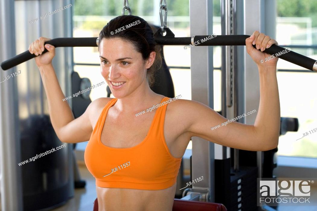 Stock Photo: Woman using exercise equipment in gym, smiling, close-up.