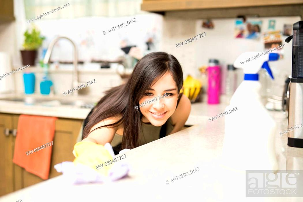Stock Photo: Close-up of smiling young housewife cleaning dirty kitchen counter with rag.