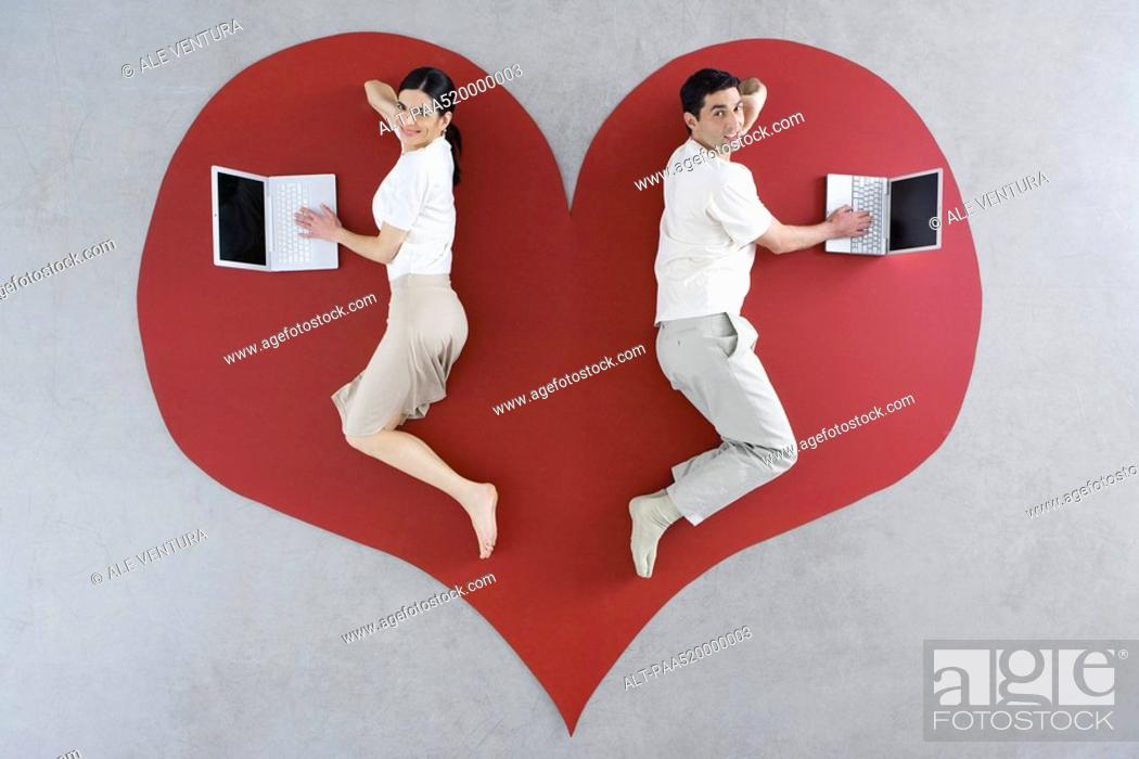 Stock Photo: Man and woman lying on large heart graphic, both using laptop computers.