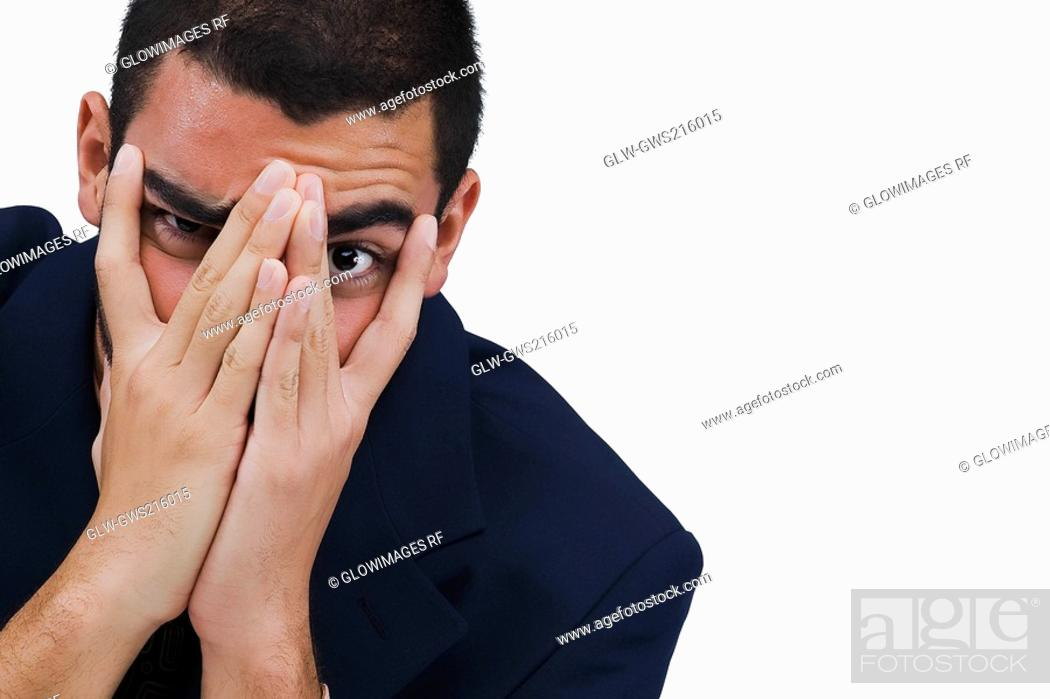 Stock Photo: Portrait of a businessman covering his face with his hands.