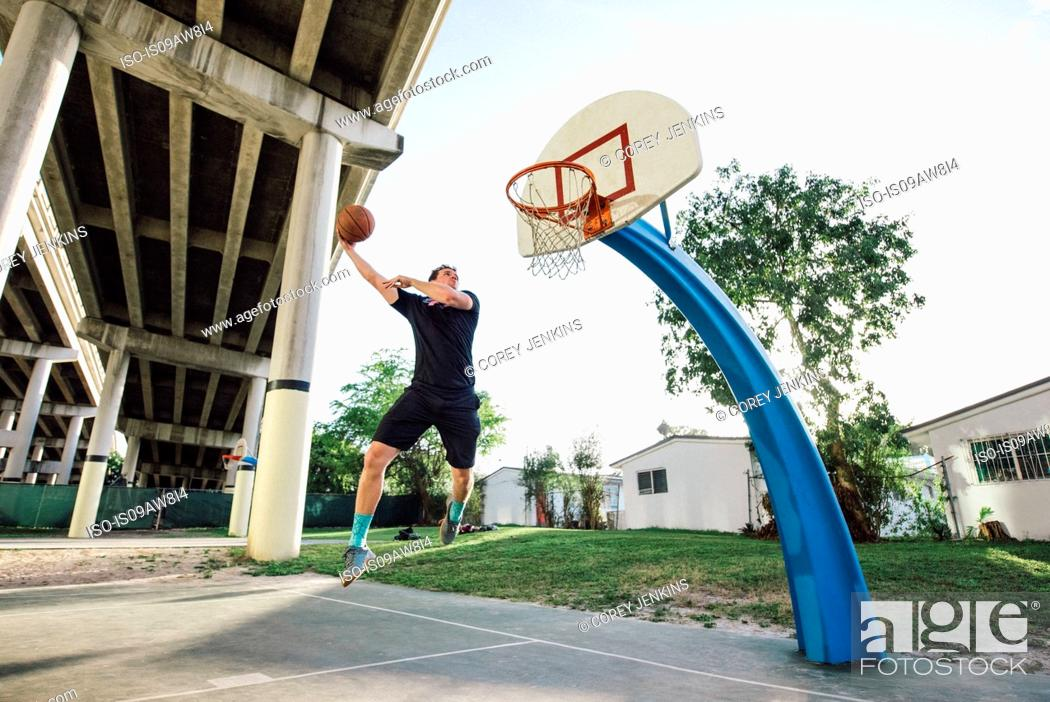 Stock Photo: Low angle view of man on basketball court in mid air jumping for basketball hoop.