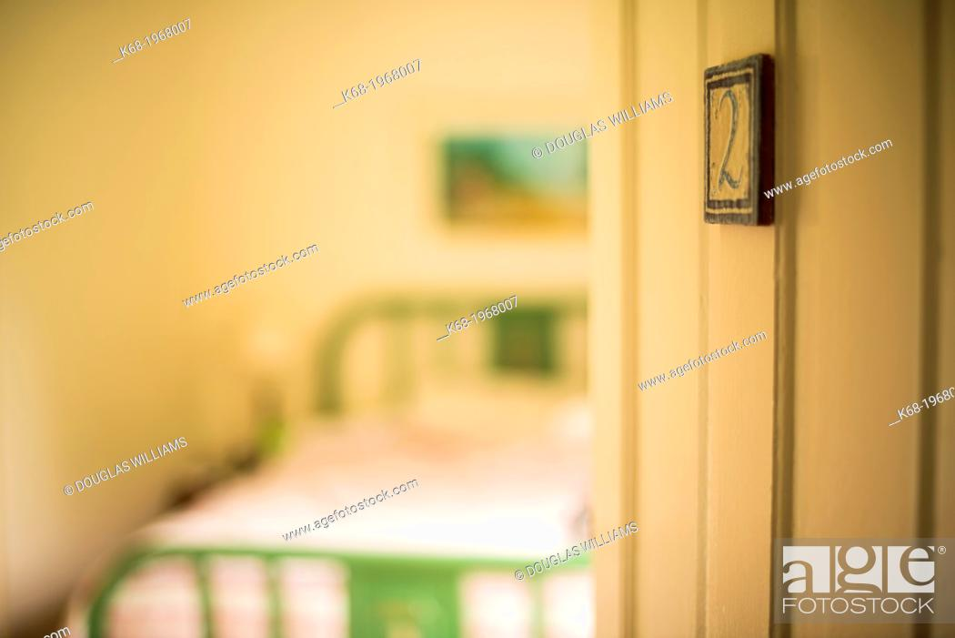 Stock Photo: A door opens to a bedroom in an historic hotel.
