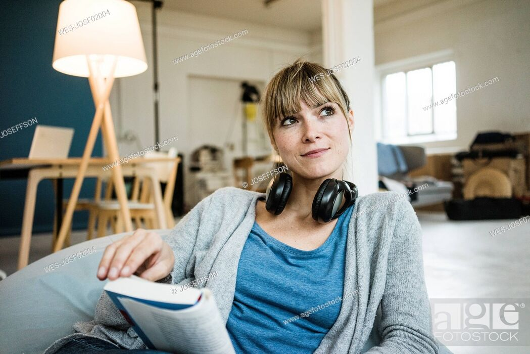 Stock Photo: Smiling woman sitting in beanbag with book and headphones.