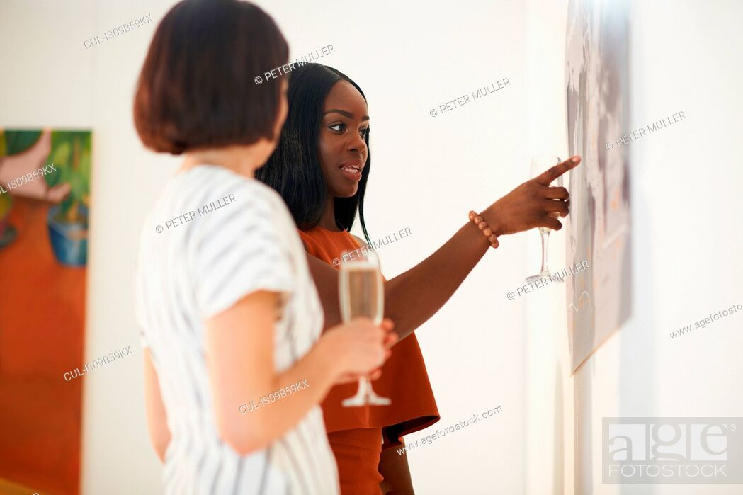 Imagen: Two women pointing at oil paintings at art gallery opening.