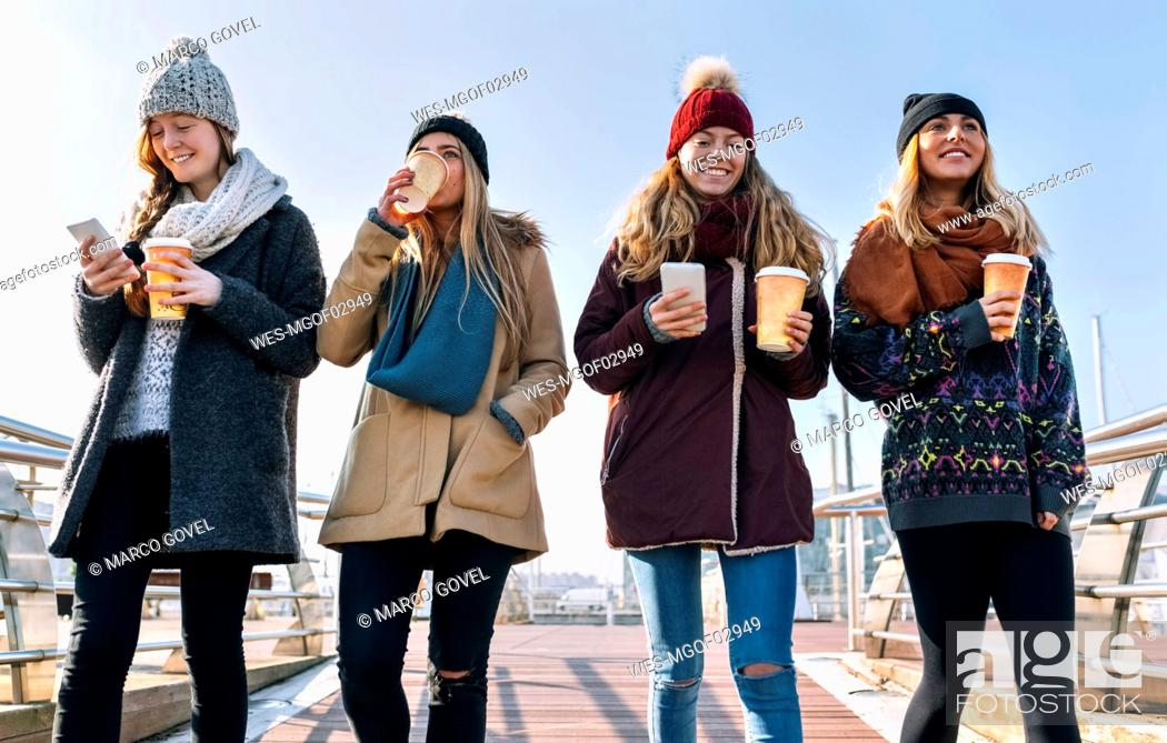 Stock Photo: Four friends with coffee to go and cell phones walking on a bridge in winter.