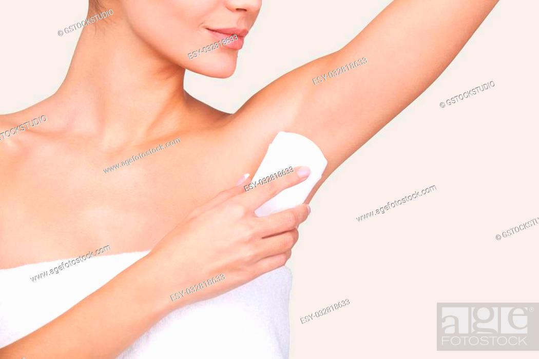 Stock Photo: Staying fresh. Cropped image of beautiful young woman wrapped in towel standing against grey background.