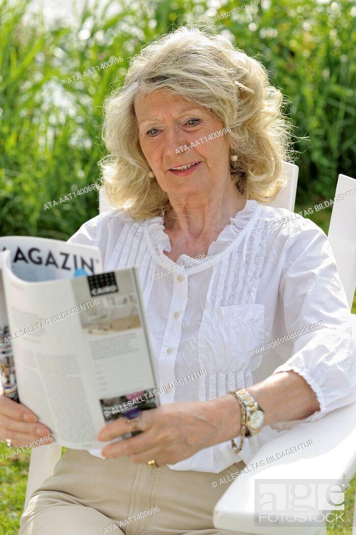 Stock Photo: Elderly woman reading a magazine.