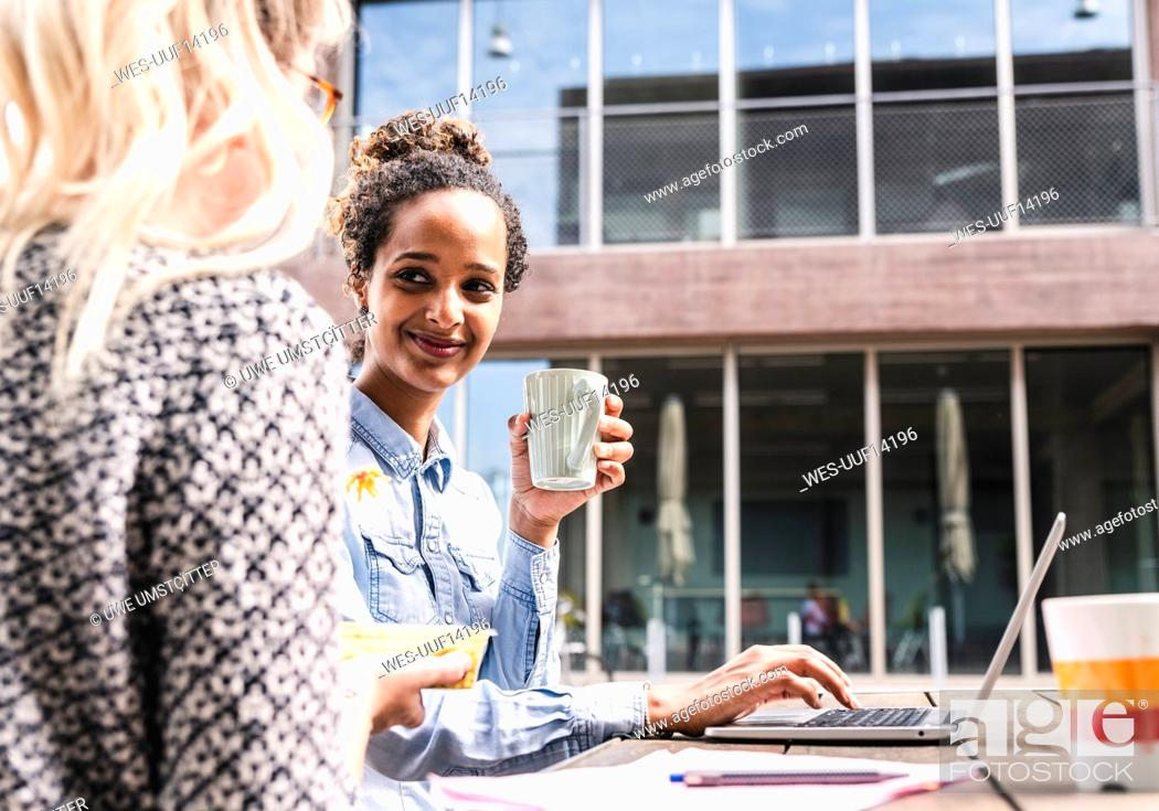 Stock Photo: Young colleagues sitting outdoors, working together, having lunch.