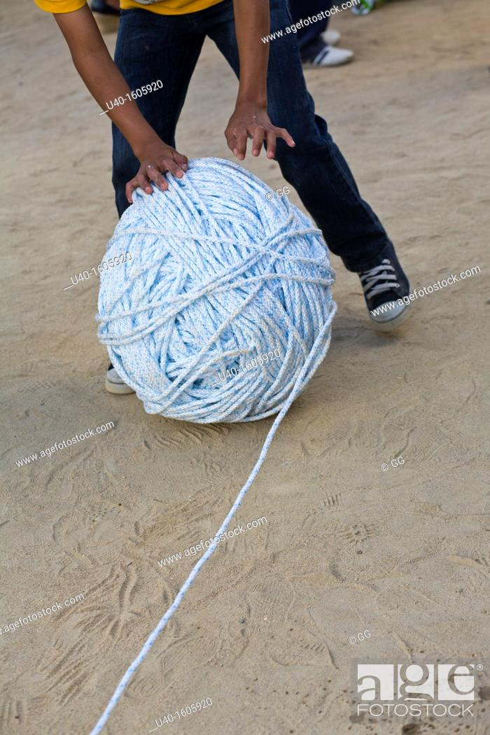 Stock Photo: Boy rolling a giant ball of string.