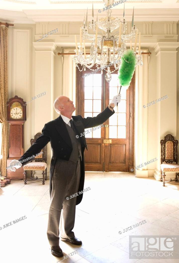 Stock Photo: Butler dusting chandelier, side view.