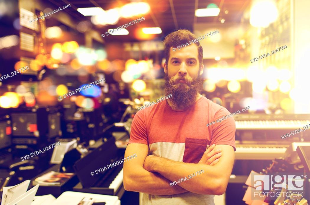 Imagen: assistant or customer with beard at music store.
