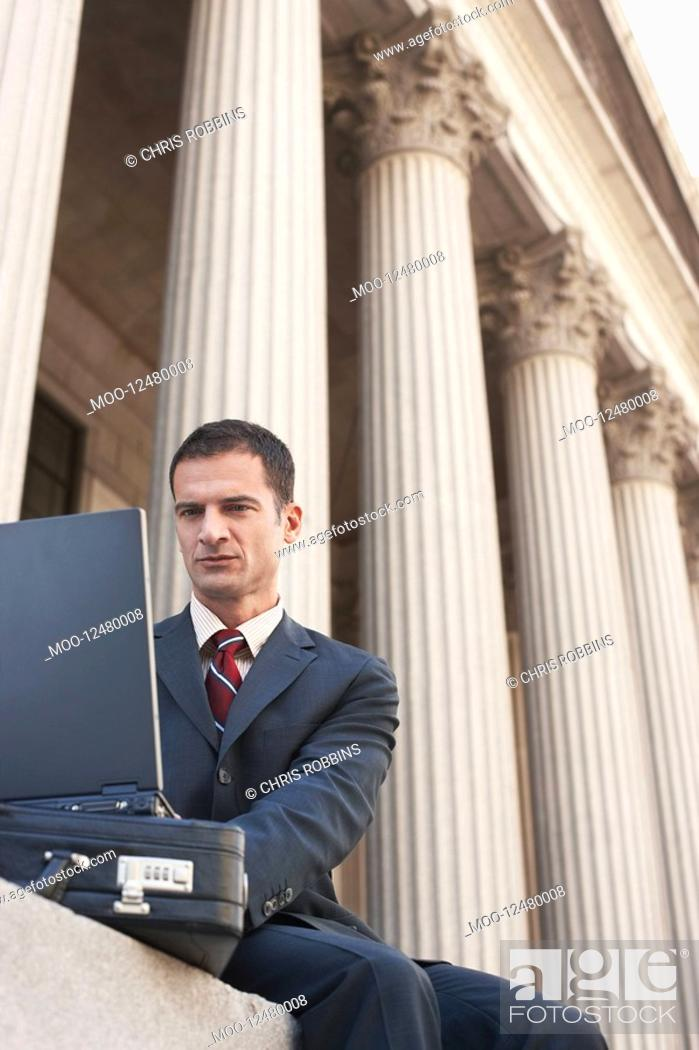 Stock Photo: Lawyer using laptop outside courthouse.