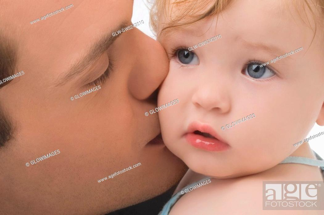 Stock Photo: Close-up of a young man kissing his daughter.