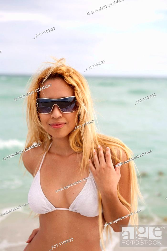 Stock Photo: A beautiful young woman in a bikini and sunglasses at the beach.