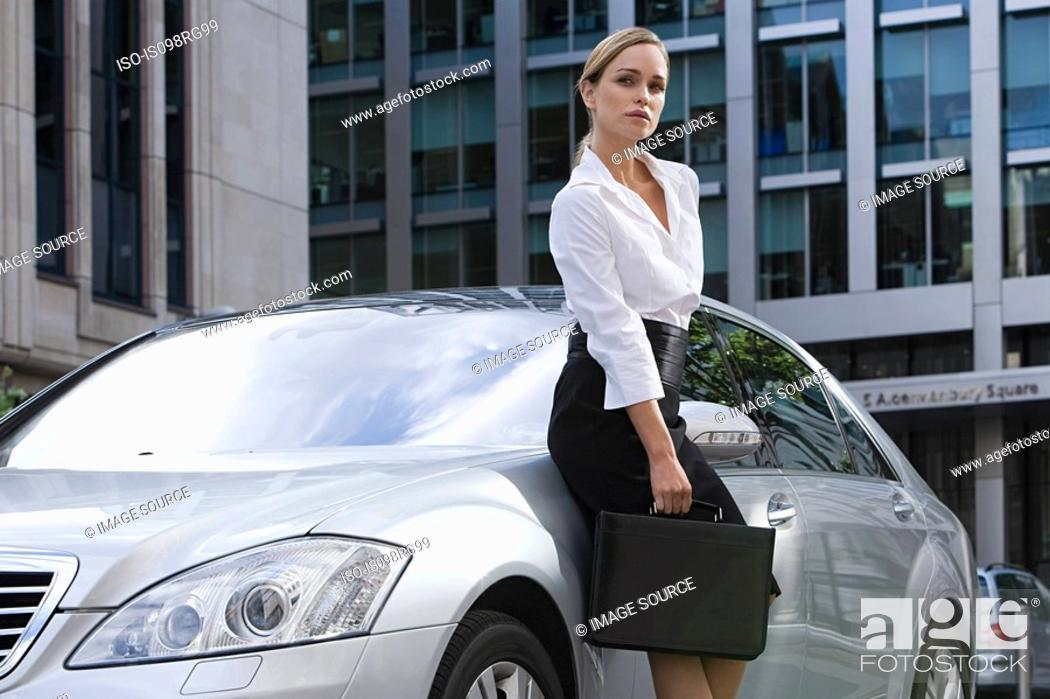 Stock Photo: Businesswoman leaning on a car.
