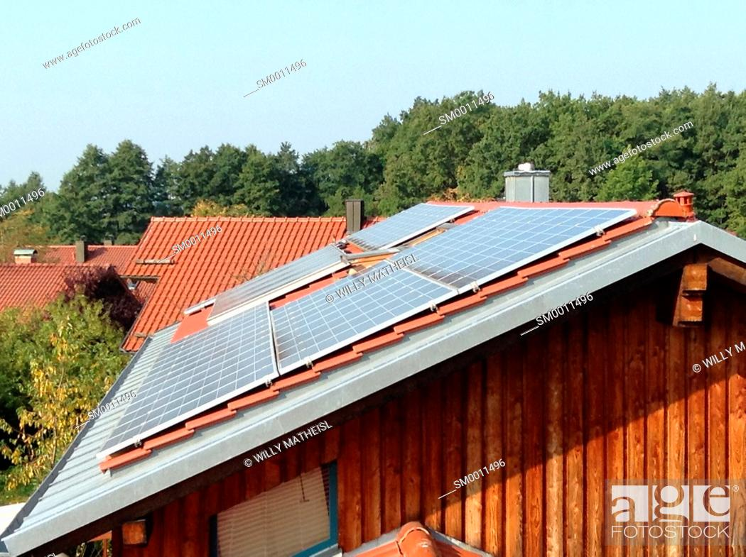 Imagen: solar pannels on a rooftop of a wooden family house, Bavaria, Germany, Europe.
