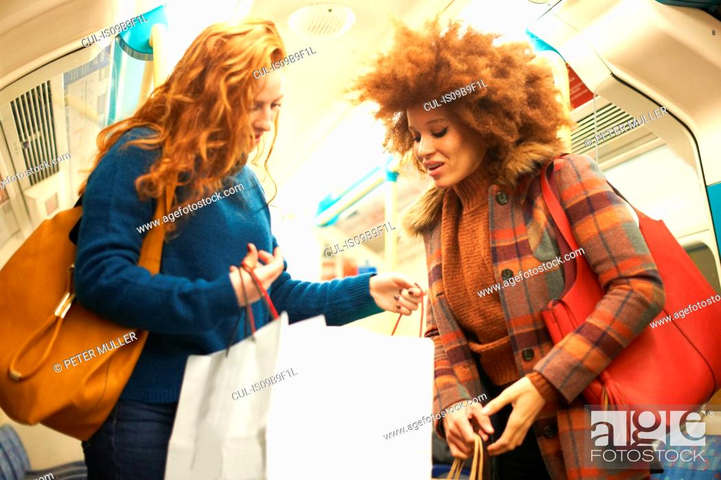 Imagen: Two young women on train, looking in shopping bags.