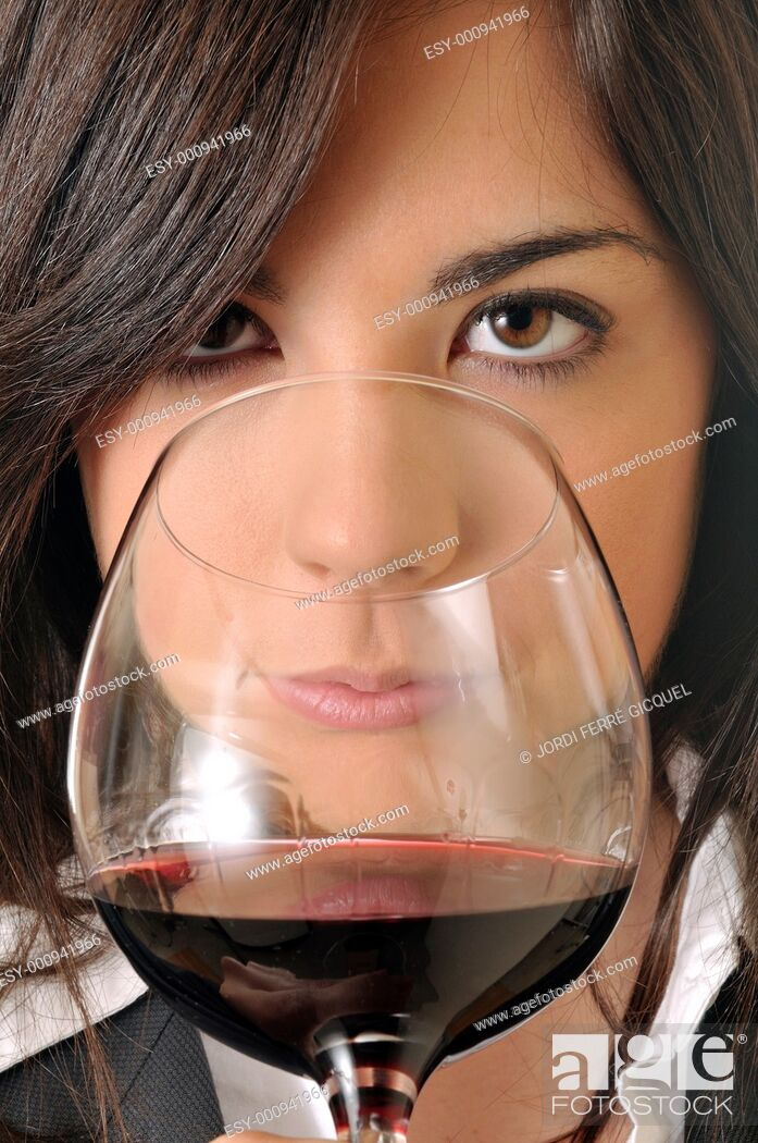 Imagen: young brown woman smelling a glass of red wine.