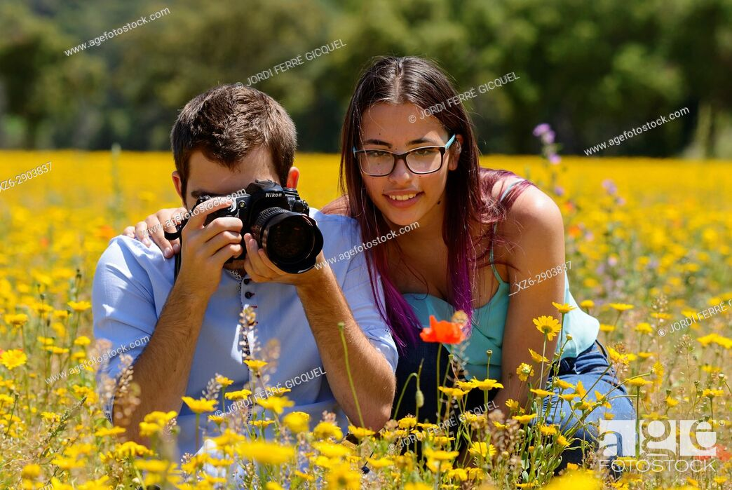 Imagen: Young man and girl, photographing flowers in a field.