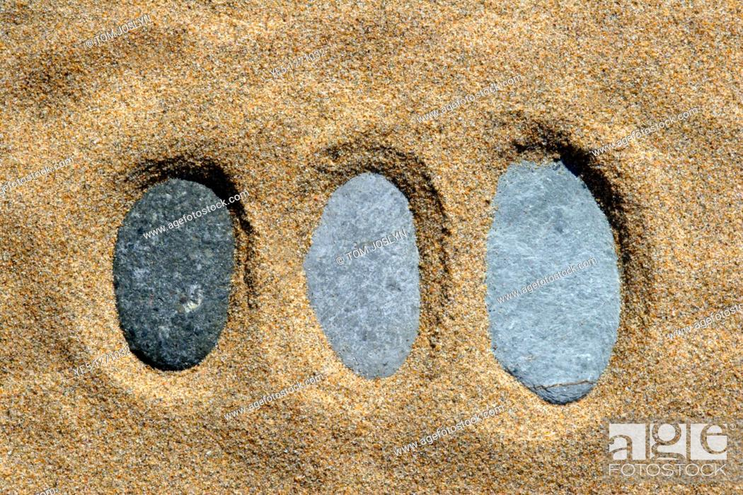 Stock Photo: Pebbles arranged in line embedded in sand.