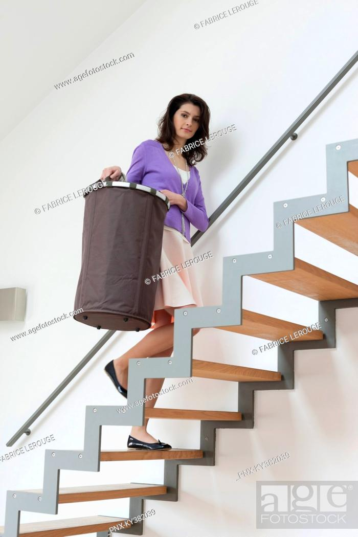 Stock Photo: Woman carrying a laundry basket.