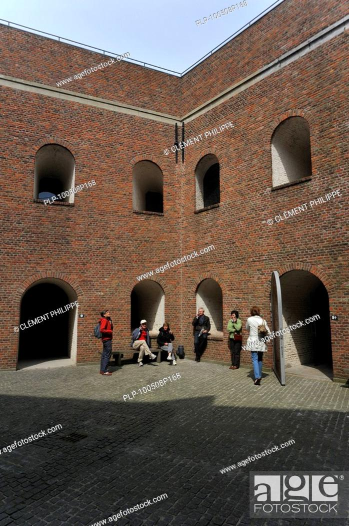 Stock Photo: Tourists with audio guides visiting the pentagonal inner court of the Fort Napoleon at Ostend, Belgium.