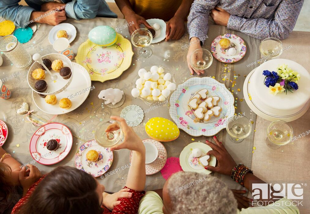 Imagen: Overhead view family enjoying Easter desserts and drinking champagne at table.