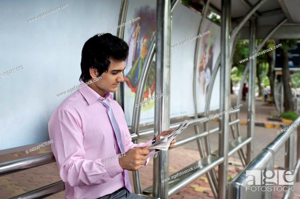 Stock Photo: Businessman reading a newspaper at a bus stop.