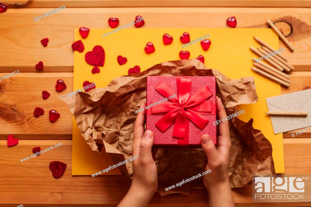 Stock Photo: A creative person packs a handmade gift in a beautiful red box tied with a ribbon. Creation. Celebrating the event.