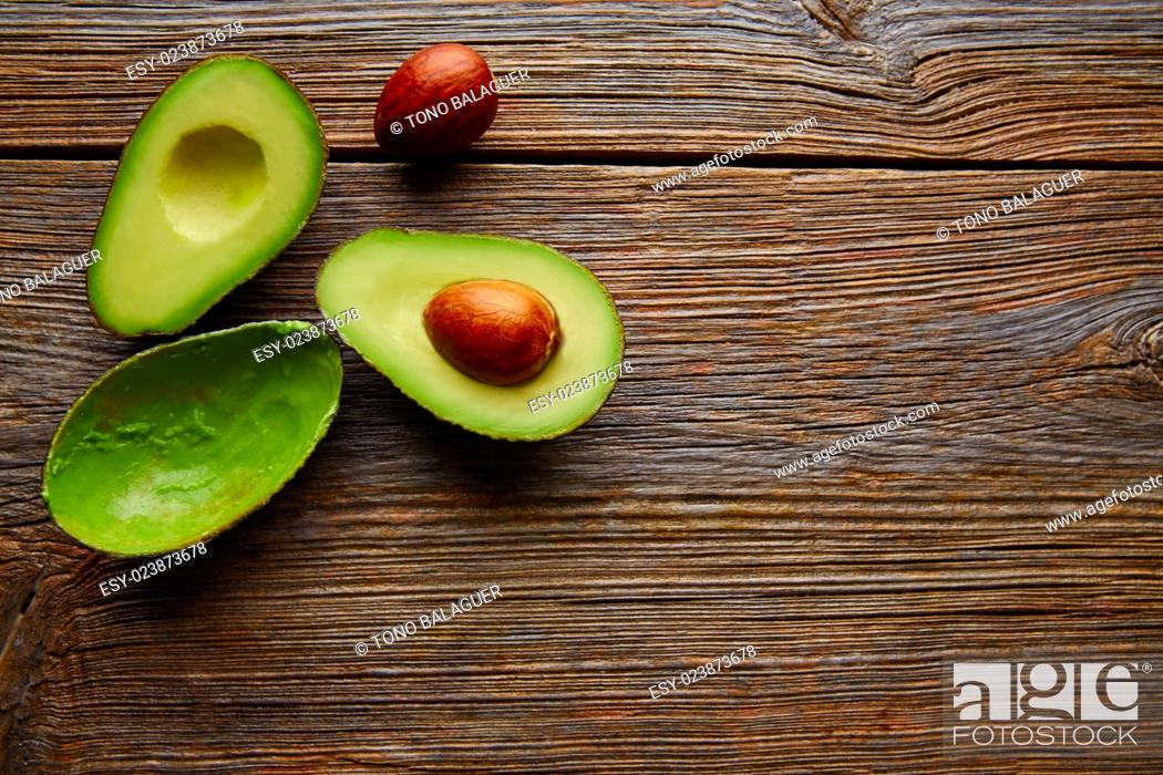 Stock Photo: avocado cut on aged wood table board cutted half.