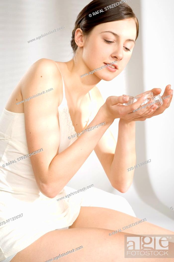 Stock Photo: young woman with ice cubes in hands.