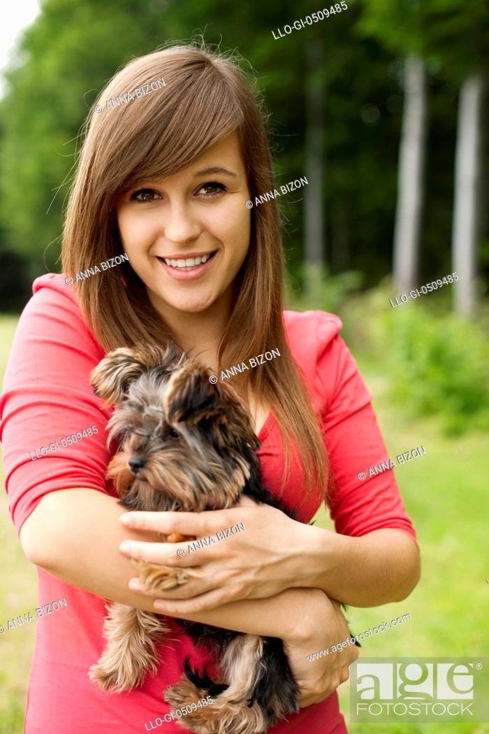 Stock Photo: Smiling woman holding cute puppy Debica, Poland.