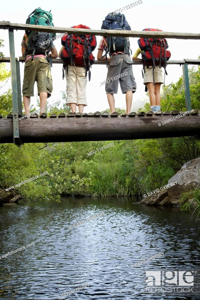Stock Photo: Four teenagers 16-17 years standing on bridge carrying backpacks looking down back view.