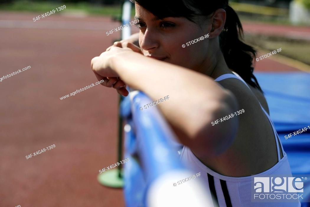 Stock Photo: Woman leaning on a high jump bar.