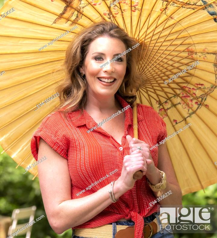 Stock Photo: A pretty 37 year old redheaded woman in a garden setting holding a parasol.