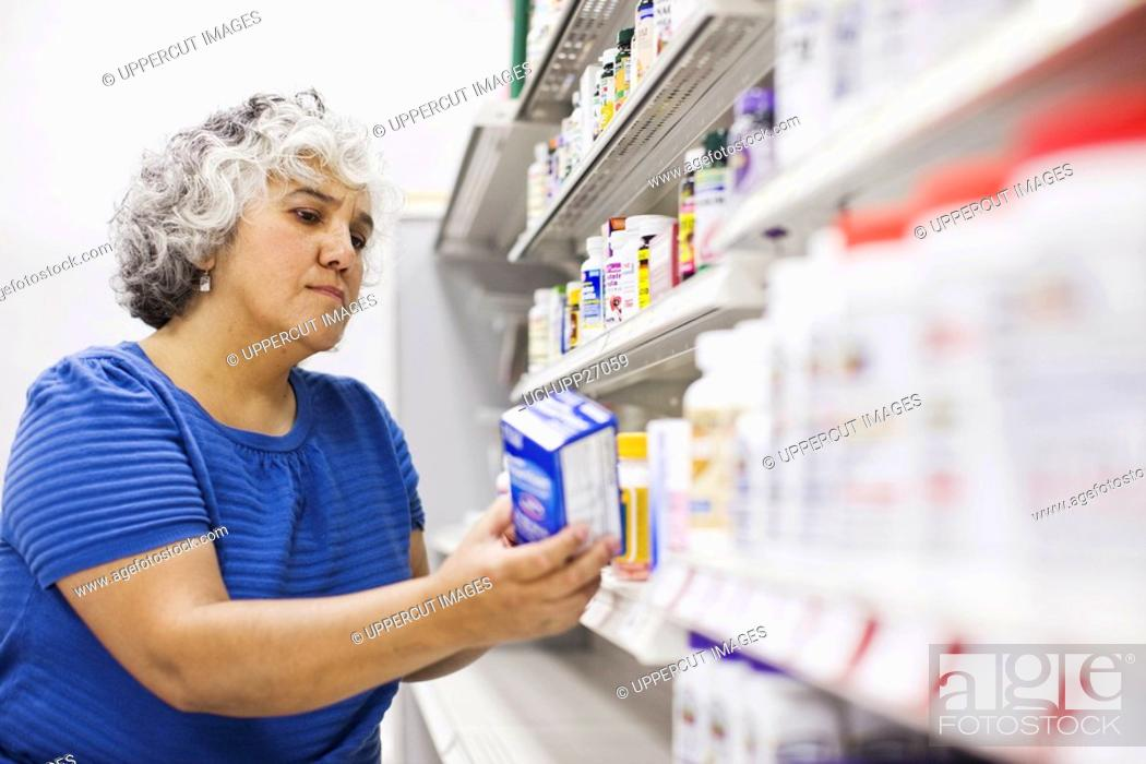 Stock Photo: Woman looking at medical product on shelf.