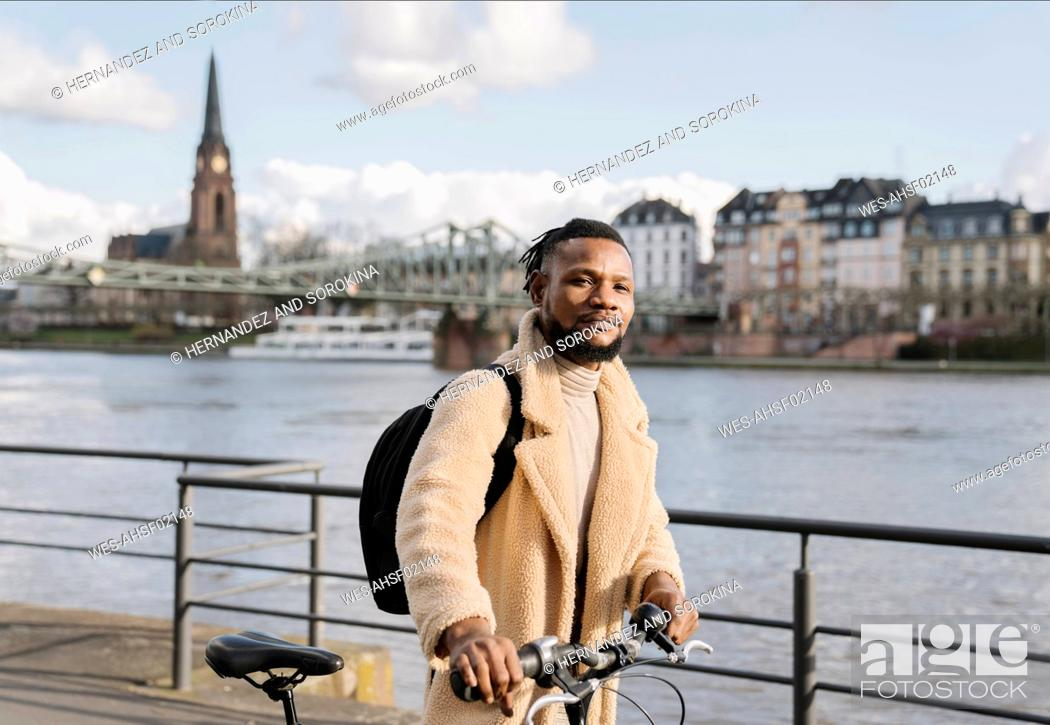 Stock Photo: Portrait of stylish man with a bicycle walking on riverbank, Frankfurt, Germany.