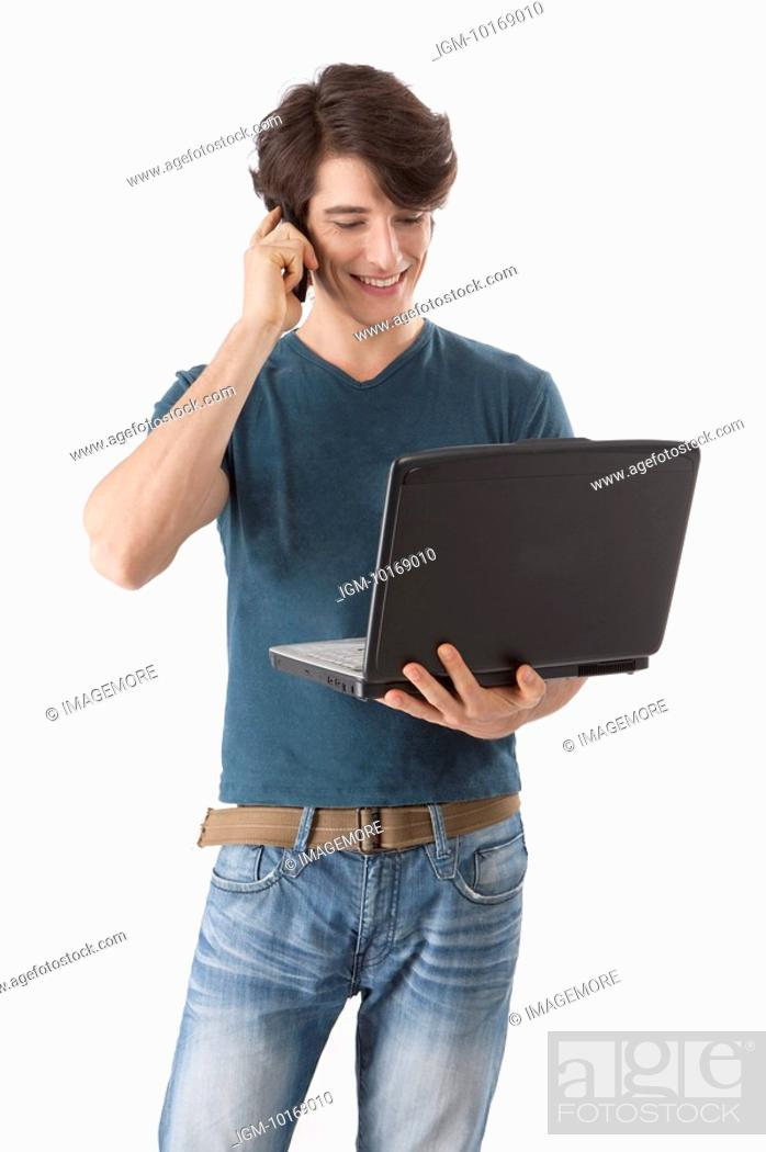 Stock Photo: Young man holding a laptop and talking on the phone.
