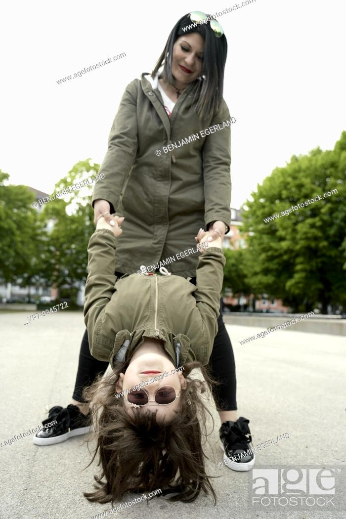 Stock Photo: daughter hanging upside down on mother's hands.