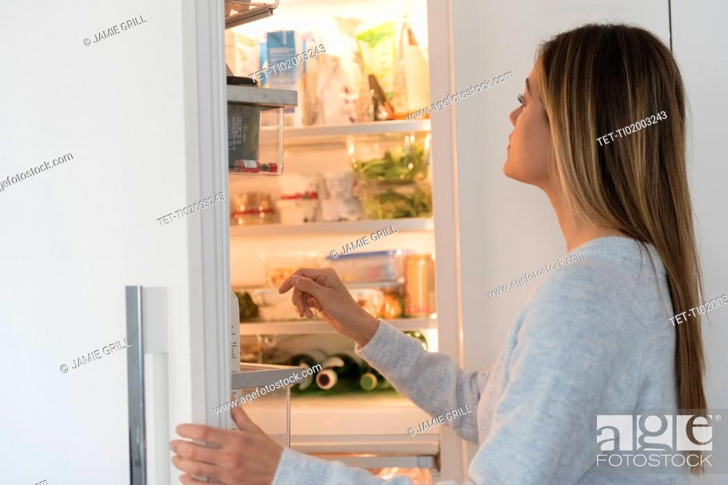 Stock Photo: Young woman looking into refrigerator.