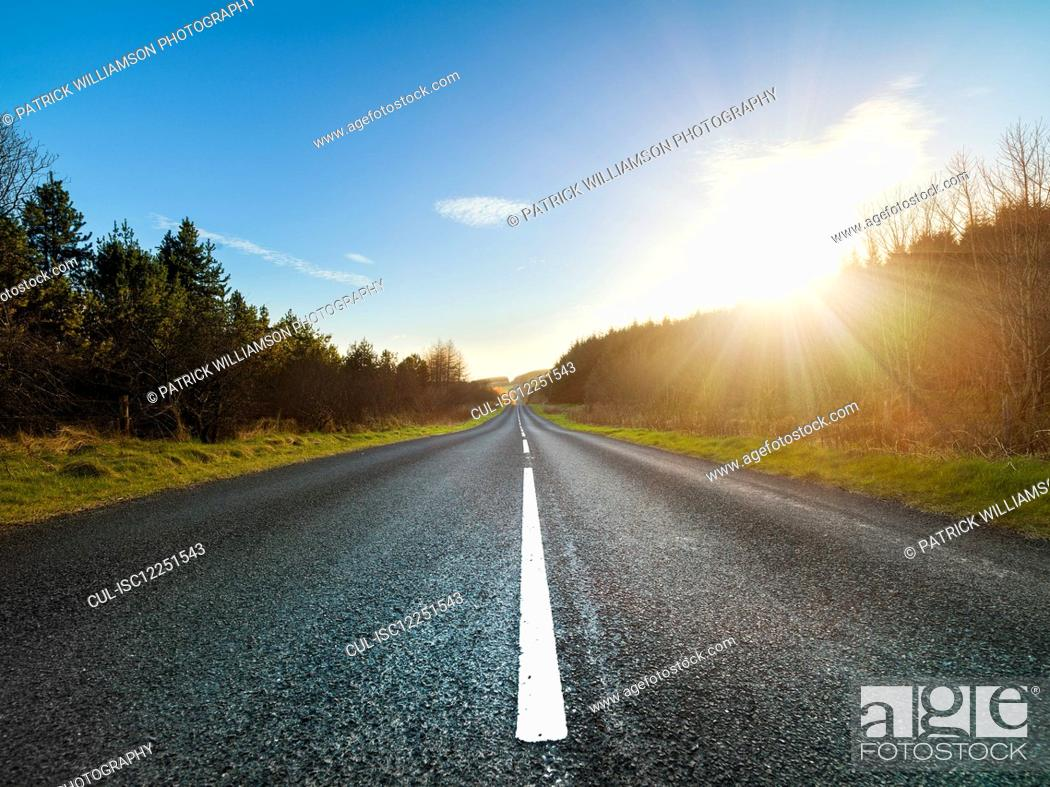 Stock Photo: View along straight country road in Ulster, Northern Ireland at sunset.